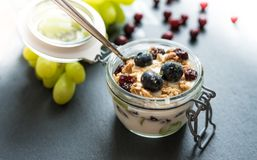 Yoghurt with grapes, meusli crumble and cranberries in jar. Yoghurt with grapes, meusli crumble and cranberries in preserving jar stock image
