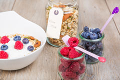 Yoghurt with home made cereals. Fresh yoghurt with home made cereals and muesli, fresh raspberry and blueberry and glass of milk on wooden textured background as royalty free stock photos