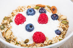 Yoghurt with home made cereals. Fresh yoghurt with home made cereals and muesli, fresh raspberry and blueberry and glass of milk on wooden textured background as royalty free stock photo