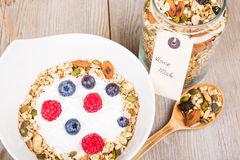 Yoghurt with home made cereals. Fresh yoghurt with home made cereals and muesli, fresh raspberry and blueberry and glass of milk on wooden textured background as stock photos