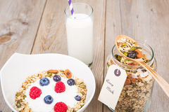 Yoghurt with home made cereals. Fresh yoghurt with home made cereals and muesli, fresh raspberry and blueberry and glass of milk on wooden textured background as royalty free stock photography