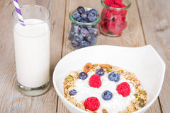 Yoghurt with home made cereals. Fresh yoghurt with home made cereals and muesli, fresh raspberry and blueberry and glass of milk on wooden textured background as stock photo