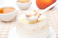 Yoghurt with honey, fresh peaches, nuts in a spoon Stock Photography