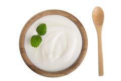 Yoghurt i en träbunke med mintkaramellbladet som isoleras på bästa sikt för vit bakgrund royaltyfri fotografi