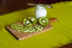 Yoghurt with kiwi. Healthy nutritious snack or breakfast on wood and green background Stock Photo