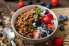 Yoghurt med bakade granola och bär i liten bunke fotografering för bildbyråer