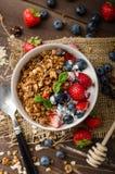Yoghurt med bakade granola och bär i liten bunke royaltyfri foto