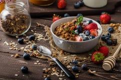 Yoghurt med bakade granola och bär i liten bunke royaltyfri fotografi