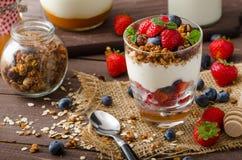 Yoghurt med bakade granola och bär i litet exponeringsglas Arkivfoto