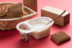 Yoghurt med chokladbollar Dubbel plast- kopp med den vita yoghurten och s?ta kanelbruna kakor arkivfoto