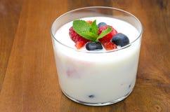 Yoghurt med den olika bär och mintkaramellen i den glass dryckeskärlen arkivfoto