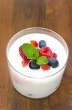 Yoghurt med den olika bär och mintkaramellen i en glass dryckeskärl royaltyfri fotografi