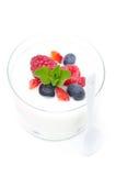 Yoghurt med den olika nya bär och mintkaramellen i en glass dryckeskärl arkivbild