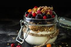 Yoghurt med granola och bär i liten krus, jordgubbar, blåbär , svart vinbär sötma hemlagad yoghurt sund mat royaltyfri foto