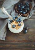 Yoghurt med granola och nya blåbär, i den glass bunken över ol Royaltyfri Foto