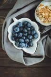 Yoghurt med granola och nya blåbär, i den glass bunken över ol Royaltyfria Bilder