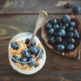 Yoghurt med granola och nya blåbär, i den glass bunken över ol Arkivfoto