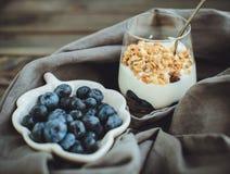 Yoghurt med granola och nya blåbär, i den glass bunken över ol Arkivbilder