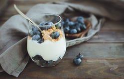 Yoghurt med granola och nya blåbär, i den glass bunken över ol Arkivbild