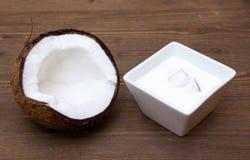 Yoghurt med kokosnöten på trä Arkivbild
