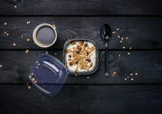Yoghurt med mysli och kaffe i en disponibel behållare Mörk träbakgrund för bästa sikt royaltyfria foton