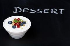 Yoghurt med nya bär på en svart bakgrund fotografering för bildbyråer