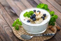 Yoghurt med nya blåbär-, banan- och mandelmuttrar Royaltyfria Bilder