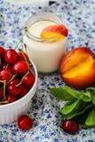 Yoghurt med persikor, körsbär och mintkaramellen royaltyfri foto