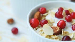 Yoghurt met Amerikaanse veenbessen, amandelen, havermeel, amandelvlokken stock videobeelden
