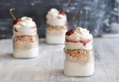 Yoghurt met muesli en aardbei op een houten lijst stock foto