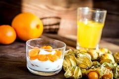 Yoghurt met physalis op houten achtergrond royalty-vrije stock foto's