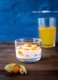 Yoghurt met physalis op houten achtergrond Stock Fotografie