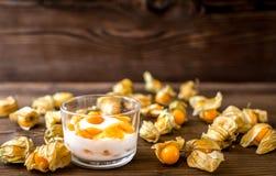 Yoghurt met physalis op houten achtergrond Stock Afbeelding