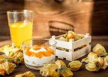 Yoghurt met physalis op houten achtergrond Stock Afbeeldingen