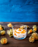 Yoghurt met physalis op houten achtergrond Royalty-vrije Stock Afbeelding