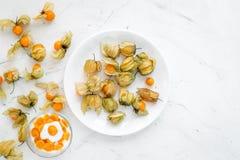 Yoghurt met physalis op steen hoogste mening als achtergrond Royalty-vrije Stock Afbeeldingen