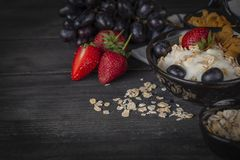 Yoghurt mix oatmeal, strawberry and grape topping in black bowl on wood table with grapes, strawberry, cornflakes and oatmeal stock images