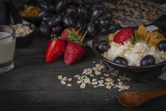 Yoghurt mix oatmeal, strawberry and grape topping in black bowl on wood table with spoon, grapes, strawberry, milk in glass, corn stock photo