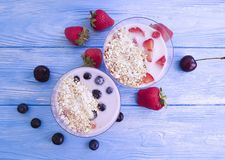 Yoghurt, oatmeal blueberry strawberry healthy delicious on a blue wooden background. Yoghurt oatmeal blueberry strawberry on a blue wooden background delicious stock photos