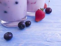 Yoghurt, oatmeal blueberry strawberry on a blue wooden background. Yoghurt oatmeal blueberry strawberry on a blue wooden background royalty free stock photo