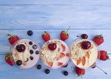 Yoghurt, oatmeal blueberry strawberry homemade dairy delicious refreshment apricot cherry on a blue wooden background. Yoghurt, oatmeal blueberry strawberry royalty free stock image