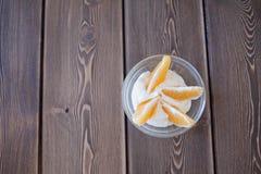 Yoghurt- och apelsinskivor i en glass maträtt på en trätabell Royaltyfria Foton