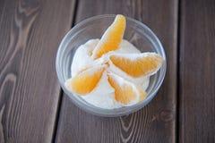 Yoghurt- och apelsinskivor i en glass maträtt på en trätabell Royaltyfria Bilder