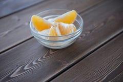 Yoghurt- och apelsinskivor i en glass maträtt på en trätabell Arkivbilder