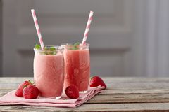 Yoghurt- och jordgubbesmoothien skorrar itu med att dricka sugrör på trätabellen arkivfoton