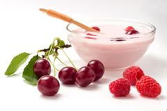 Yoghurt from a raspberry and a cherry in a glass bowl with a wooden spoon.  Royalty Free Stock Photography