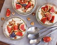 Yoghurt som överträffas med nya fikonträd och grillade hasselnötter Royaltyfri Foto