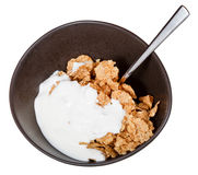 Yoghurt and spoon into bowl of cereal. Top view of yoghurt and spoon into bowl of cereal isolated on white background Royalty Free Stock Photography