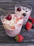 Yoghurt, strawberry, cherry, morning cereal muesli blueberry glass on a black wooden background. Yoghurt muesli , strawberry, cherry, blueberry glass on a black stock photography
