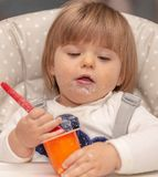 yoghurt zitting eating vuil Baby girl stock foto